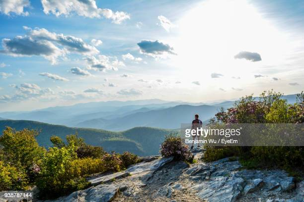rear view of male hiker standing on cliff against mountains - outdoor pursuit stock pictures, royalty-free photos & images