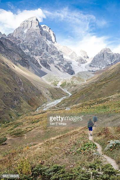 Rear view of male hikers in mountain landscape, Ushba, Svaneti, Georgia