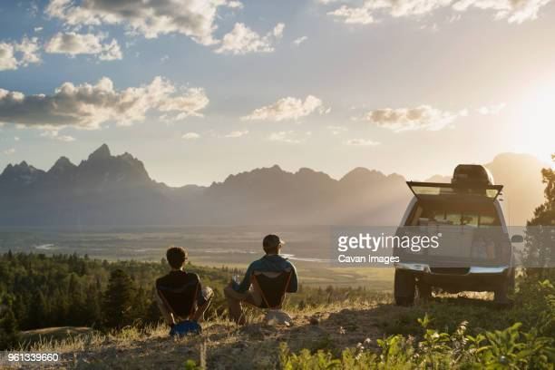 rear view of male hikers relaxing on reclining chair in field - attività all'aperto foto e immagini stock