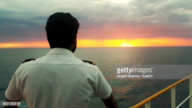 rear view of male navy officer on boat in sea during sunset - navy stock pictures, royalty-free photos & images