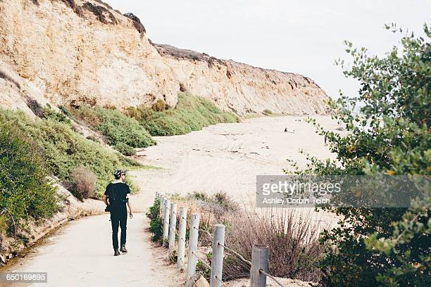 Rear view of male photographer strolling to beach, Crystal Cove State Park, Laguna Beach, California, USA