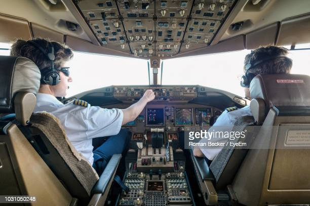 rear view of male pilots flying airplane - pilot stock pictures, royalty-free photos & images