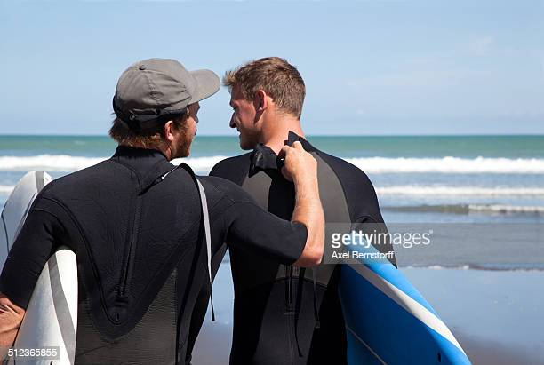 Rear view of male surfer checking his friends wet suit zipper
