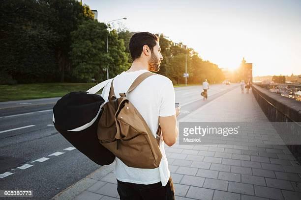 Rear view of male tourist looking away while walking on sidewalk of bridge