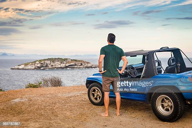 Rear view of male tourist looking out to Branca island, Buzios, Rio de Janeiro, Brazil