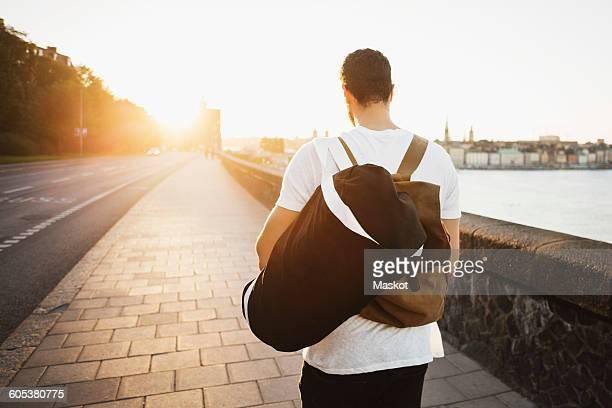Rear view of male tourist walking on sidewalk of bridge
