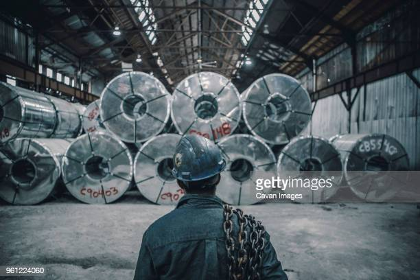 Rear view of male worker carrying chain standing in front of rolled up steel sheets at factory