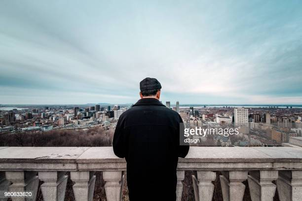 Rear view of man admiring city skyline of Montreal from balcony