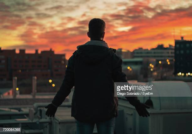 Rear View Of Man Against Cityscape At Dusk