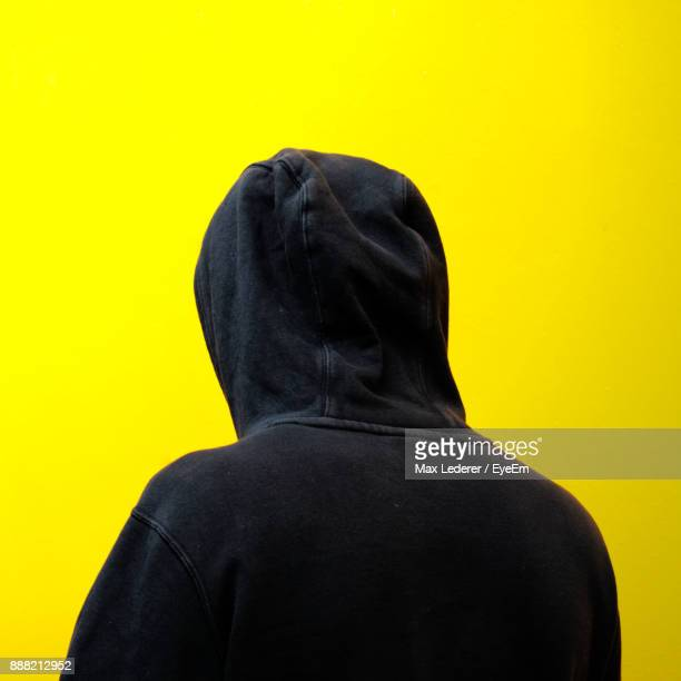 rear view of man against yellow background - hooded shirt stock pictures, royalty-free photos & images