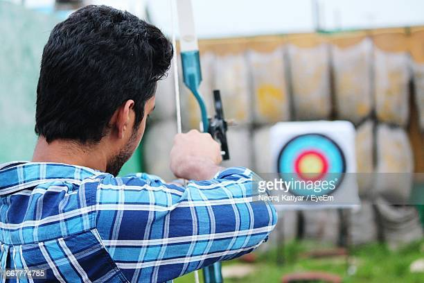 Rear View Of Man Aiming At Target With Bow And Arrow