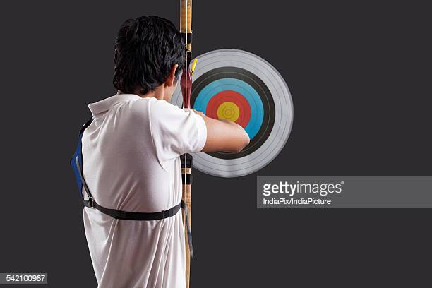 rear view of man aiming target with bow against black background rear view of man aiming target with bow against black background - 弓術 ストックフォトと画像