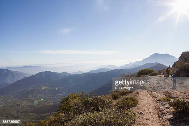 'Rear view of man and two sons hiking dirt track in Andes, Valparaiso, Chile'