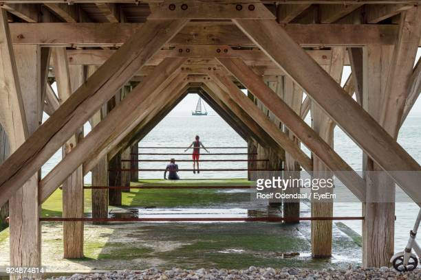Rear View Of Man And Woman By Sea Seen Through Wooden Pier