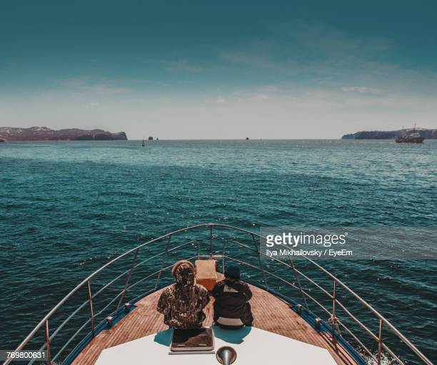 Rear View Of Man And Woman In Boat On Sea Against Sky