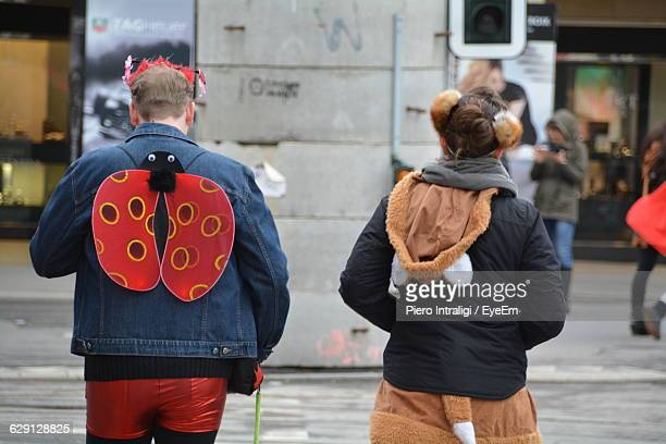Rear View Of Man And Woman In Costume On Street