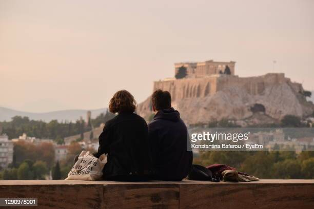 rear view of man and woman looking at buildings against sky - greece stock pictures, royalty-free photos & images