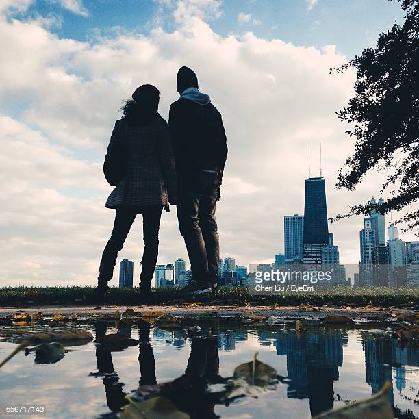 Rear View Of Man And Woman Looking At Cityscape Against Cloudy Sky