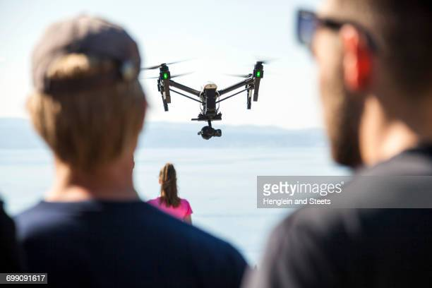Rear view of man and woman looking at drone flying mid air over coast, Split, Dalmatia, Croatia