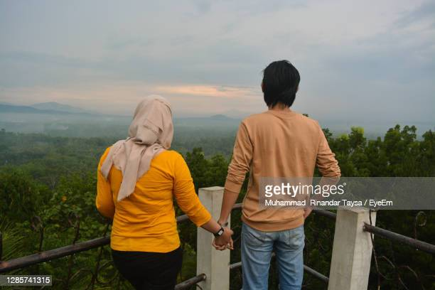 rear view of man and woman looking at view - honeymoon stock pictures, royalty-free photos & images
