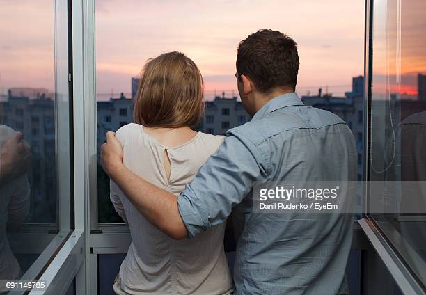 Rear View Of Man And Woman Looking Through Window During Sunset