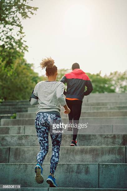 Rear view of man and woman moving up staircase