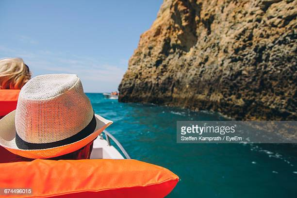Rear View Of Man And Woman On Boat Sailing In Sea