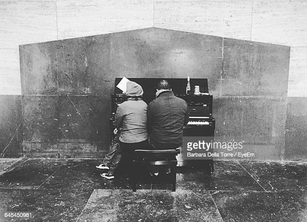 Rear View Of Man And Woman Playing Grand Piano At Milano Centrale Railway Station