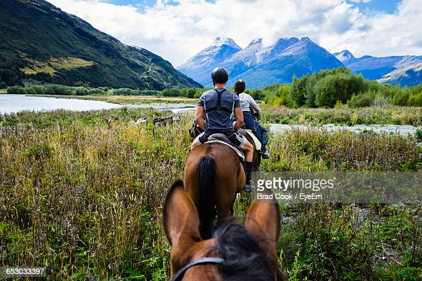 Rear View Of Man And Woman Riding Horses Towards River And Mountains