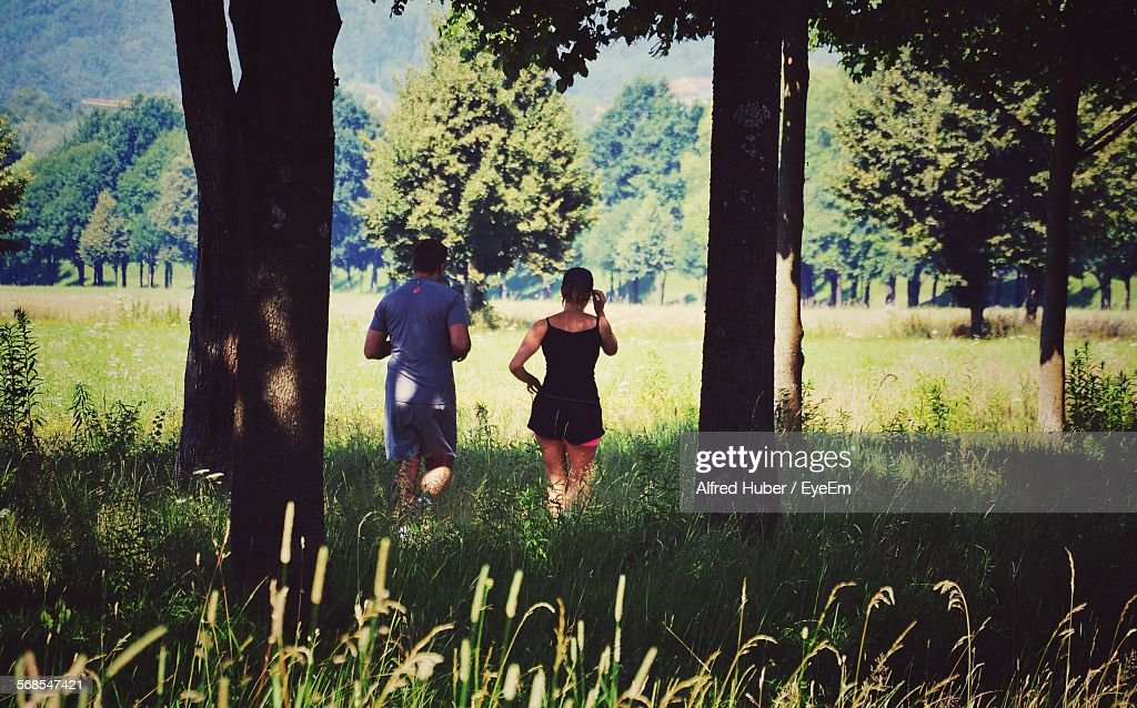 Rear View Of Man And Woman Running In Park : Stock Photo