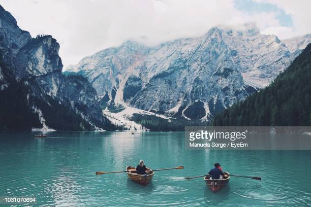 rear view of man and woman sailing boats in lake - pragser wildsee stock pictures, royalty-free photos & images