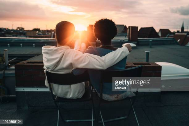 rear view of man and woman sitting on building rooftop during sunset - sunset stock pictures, royalty-free photos & images