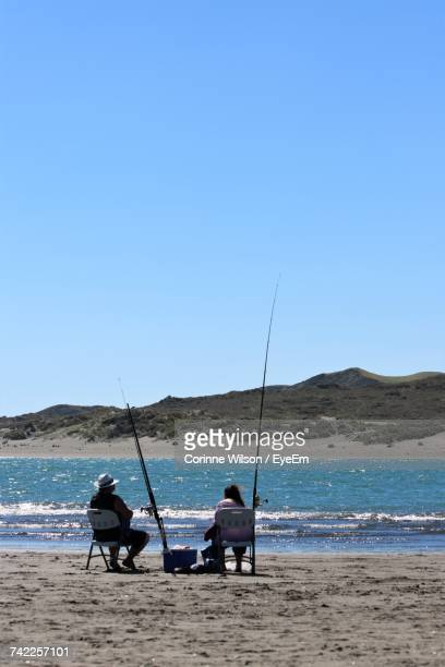 rear view of man and woman sitting on chair by fishing rod at beach - corinne paradis ストックフォトと画像