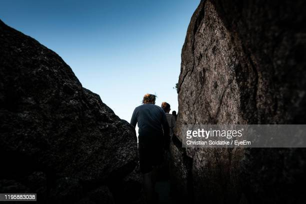 rear view of man and woman standing by rock - christian soldatke stock pictures, royalty-free photos & images