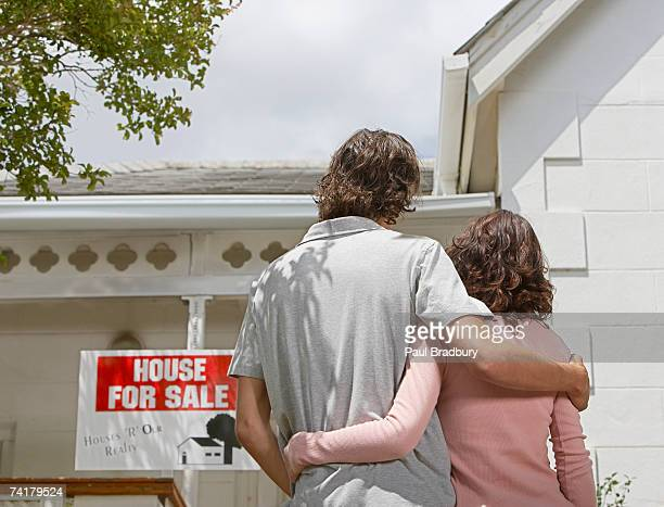 Rear view of man and woman standing in front of house with for sale sign