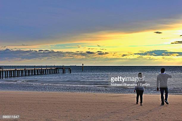 Rear View Of Man And Woman Walking At Beach Against Sky During Sunset