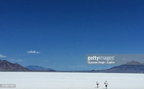 rear view of man and woman walking at bonneville salt flats against sky - bonneville salt flats stock pictures, royalty-free photos & images
