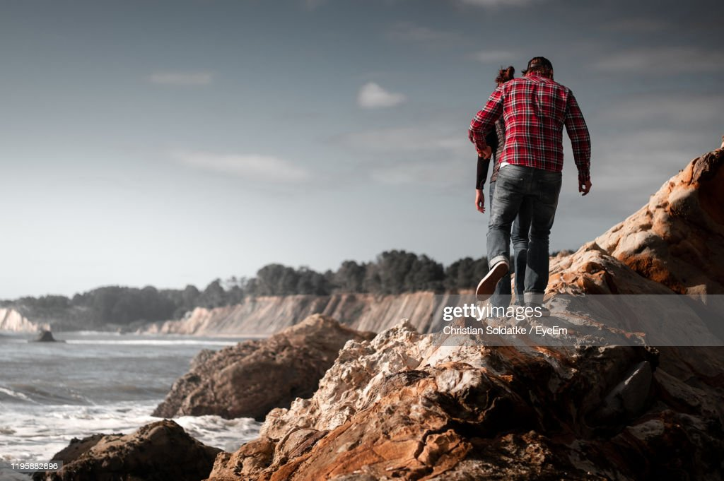 Rear View Of Man And Woman Walking On Rock Against Sky : Stock-Foto