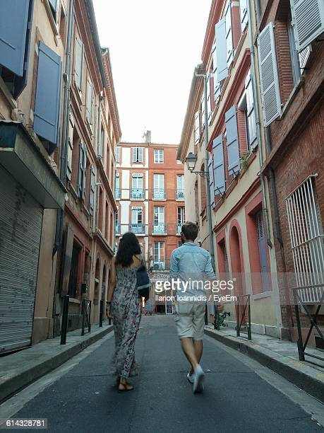 Rear View Of Man And Woman Walking On Street Amidst Buildings In City
