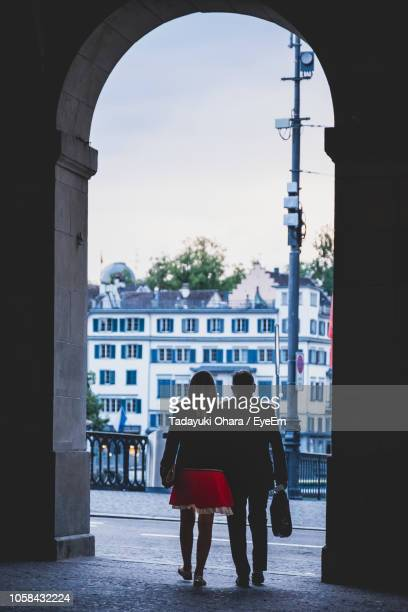 rear view of man and woman walking through arch - arch stock pictures, royalty-free photos & images