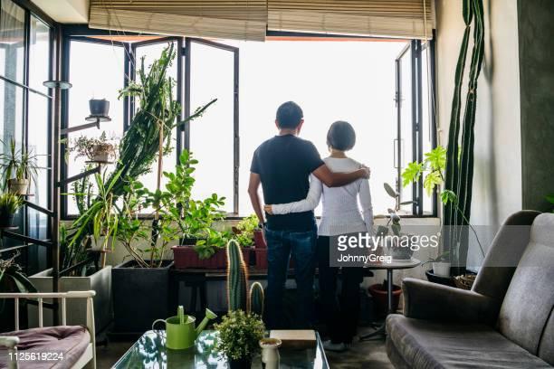 achteraanzicht van man en vrouw met de armen om elkaar heen door raam - serene mensen stockfoto's en -beelden