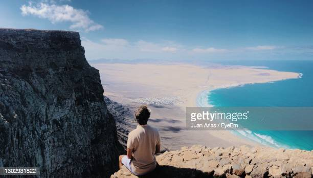 rear view of  man astringente on cliff over beach - lanzarote stock pictures, royalty-free photos & images