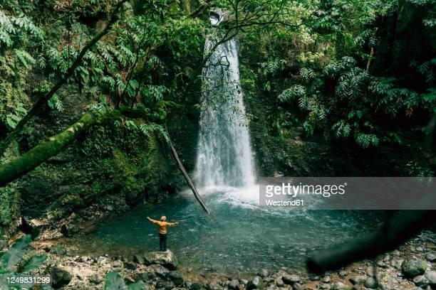 rear view of man at a waterfall on sao miguel island, azores, portugal - azores fotografías e imágenes de stock