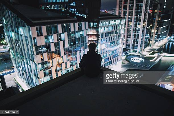 Rear View Of Man At On Rooftop At Night