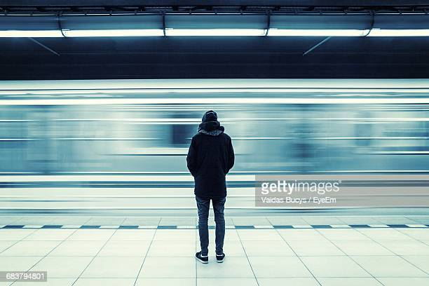 rear view of man at subway station platform - subway platform stock pictures, royalty-free photos & images