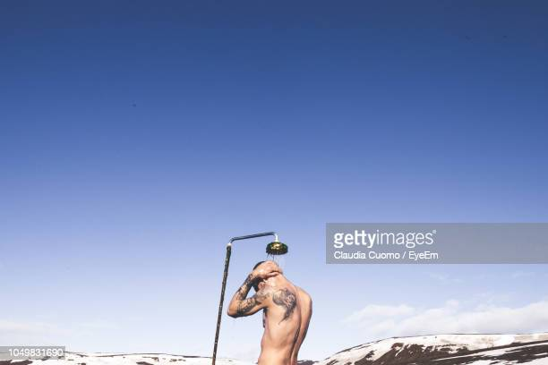 rear view of man bathing against blue sky - homme sous la douche photos et images de collection