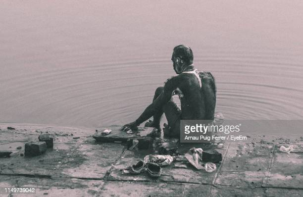 rear view of man bathing at riverbank - taking a bath stock pictures, royalty-free photos & images