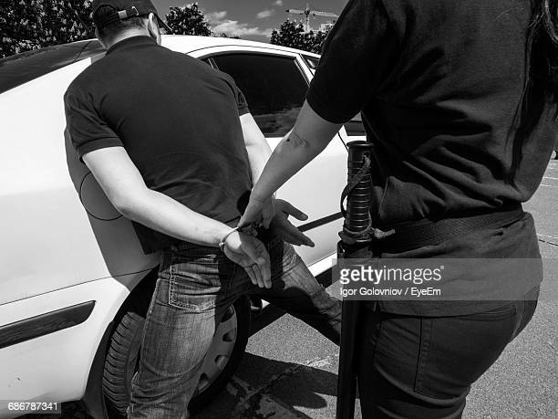 rear view of man being arrested by policewoman - igor golovniov stock pictures, royalty-free photos & images