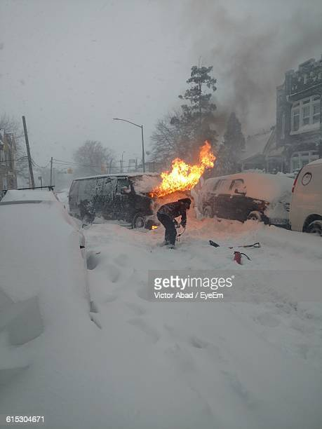 Rear View Of Man By Burning Car On Snowcapped Street