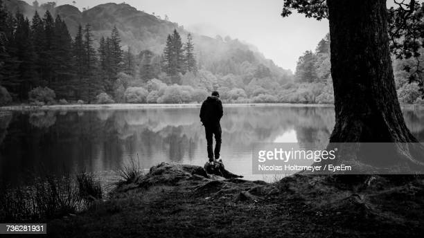 Rear View Of Man By Lake Against Sky